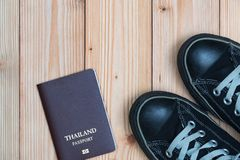 Thailand traveler's Passport and sneakers ready to travel on woo. Den floor, top view with copy space, Travel and vacation concept stock photo
