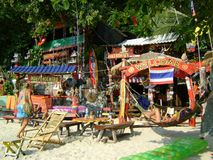 Thailand tropical sand sea beach bar huts colorful furniture. Beautiful tropical colorful Thai beach hut with sand and sea tropical trees and mountains in the stock images