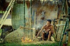 Thailand-Vater, der handgemachten Korbbambus oder Fischereiausrüstung bearbeitet Lizenzfreie Stockfotografie
