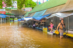 Thailand village flood. Thailand - July 27, 2011: flooded road and smashed shops in a river of mud during the tropical storm Village along the way to Chiang Rai royalty free stock images