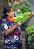 Thailand Water Festival Woman Sprays Tourists. Stock Photo