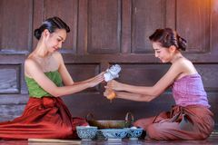 Thailand women dressed in ancient Thailand are helping to make the dessert of Thailand, candy doonghiib, golden ball candy. Candy FOI stock photography