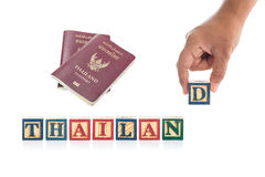THAILAND write in colorful wood alphabet blocks and hand holding D with Thailand passport isolated on whit Stock Image
