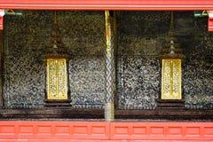 Thailändische Artkunst-Malereiwand und thailändischer Tempel der goldenen Fenster schlagen Lizenzfreie Stockfotos
