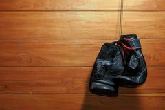 Thailändische Boxhandschuhe Muay, die an der hölzernen Wand hängen Stockbild