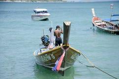 Thailändischer Mann kontrollieren und reparieren das hölzerne Fischereibootsschwimmen Lizenzfreie Stockfotografie