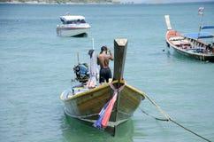 Thailändischer Mann kontrollieren und reparieren das hölzerne Fischereibootsschwimmen Lizenzfreies Stockbild
