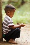 Thailändisches Kind, das kleinen Vogel hält Lizenzfreies Stockbild
