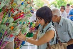 Thailändsk kvinna som donerar i donationträdet i den Visakha Bucha dagen Arkivfoton