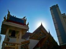Thailändsk tempel under blå himmel med soluppgång överst av byggnad Royaltyfri Bild