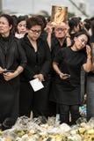 Thailändskt folk som sjunger hyllningssången av konungen Arkivfoto