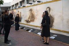 Thais в черных оплакивая одеждах сфотографировано на стене с изображением мертвого короля Bhumibol Adulyadej Часть funer Стоковые Фото