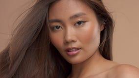 Thais Aziatisch model met natuurlijke make-up op beige achtergrond stock videobeelden