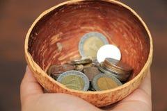 Thais Baht van het geldmuntstuk in kokosnotenshell stock afbeeldingen