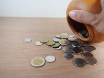 Thais Bahtmuntstuk, die geld in gebakken kleikruik besparen Royalty-vrije Stock Fotografie
