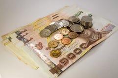 Thais Geld, 1000 Bahtbankbiljetten en muntstuk op witte achtergrond Stock Afbeelding