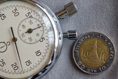 Thais muntstuk met een benaming van Baht 10 en chronometer op grijze denimachtergrond - bedrijfsachtergrond Royalty-vrije Stock Fotografie