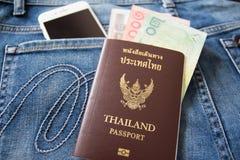 Thais paspoort in zak van jeans stock afbeeldingen