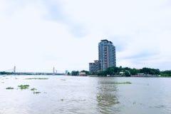 Thais Rivieroeverflatgebouw met koopflats achter de brug stock afbeelding