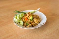 Thais voedsel - gebraden rijst op witte schotel met houten achtergrond Stock Afbeeldingen