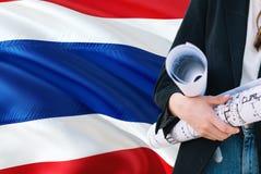 Thaise de holdingsblauwdruk van de Architectenvrouw tegen golvende de vlagachtergrond van Thailand Bouw en architectuurconcept stock foto