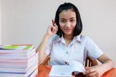 Thaise jonge volwassen studente in eenvormige lezing een boek Stock Fotografie