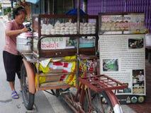 Thaise oude vrouw die gestoomde gevulde broodjes in pot voorbereiden die druk op fiets de met drie wielen van de voedselwinkel vo royalty-vrije stock foto