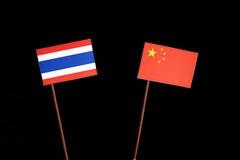 Thaise vlag met Chinese vlag op zwarte stock afbeeldingen