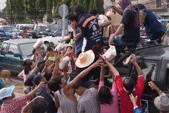 Thaise vrijwilliger die wat voedselbrood en water geeft Royalty-vrije Stock Foto's