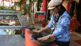 Thaise vrouw die dichtbije greep van de Chinese stijl van het gootsteenmessing voor gelukkige zegen wrijven stock footage