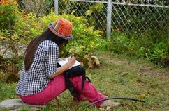 Thaise vrouwen die boek schrijven bij tuin Royalty-vrije Stock Fotografie