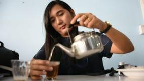 Thaise vrouwenzitting en Thaise stijl van de drank de hete thee in restaurant
