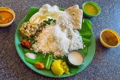 Thali indio tradicional del plato con arroz y verduras picantes en hoja de palma Aún-vida asiática de la comida Fotos de archivo libres de regalías