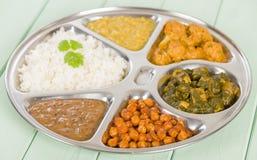 Thali. South Asian selection of vegetarian curries and rice served in a traditional dish. Taka dahl, gobi masala, palak paneer, chana masala and dahl makhani Royalty Free Stock Photography