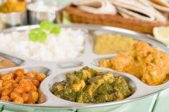 Thali. South Asian selection of vegetarian curries and rice served in a traditional dish. Taka dahl, gobi masala, palak paneer, chana masala and dahl makhani Royalty Free Stock Image