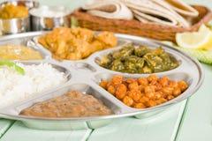 Thali. South Asian selection of vegetarian curries and rice served in a traditional dish. Taka dahl, gobi masala, palak paneer, chana masala and dahl makhani Stock Image