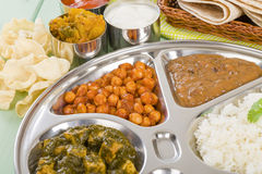 Thali. South Asian selection of vegetarian curries and rice served in a traditional dish. Taka dahl, gobi masala, palak paneer, chana masala and dahl makhani Royalty Free Stock Images