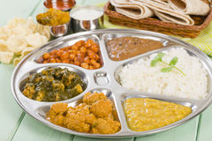 Thali. South Asian selection of vegetarian curries and rice served in a traditional dish. Taka dahl, gobi masala, palak paneer, chana masala and dahl makhani Royalty Free Stock Photography