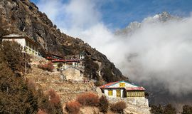 Thame gompa with prayer flags - monastery in Khumbu. Thame gompa with prayer flags and buddhist symbols - monastery in Khumbu valley on three passes trek, Mount Royalty Free Stock Images