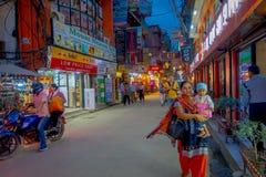 THAMEL,加德满都尼泊尔- 2017年10月02日:走和买在街道的夜观点的未认出的人民  库存照片