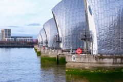 Thames Barrier with a waterfront apartment in the background Royalty Free Stock Photography