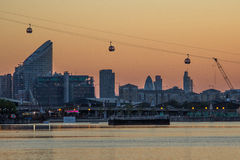 Thames Cable Car over Docklands at sunset. Gondolas of The Emirates Air Line cable car in Greenwich and London Gerkin and Finance district in background Stock Image