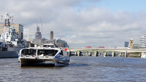 Thames Clipper boat and red busses on London Bridge. Clipper boat on Thames river and red busses on London Bridge in the city Royalty Free Stock Photo