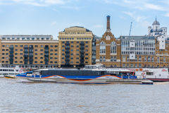 Thames Clippers. River bus service on the River Thames in London. May 2017 Butlers Wharf Warehouse at river front Royalty Free Stock Image