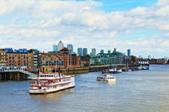 Thames River cruise boats London panorama United Kingdom. Luxury charters boats navigating on Thames River along historic Wapping bank, looking east from the royalty free stock photos