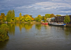 Thames River, Windsor, England. Barges and buildings line the shore of the Thames River in Windsor, the United Kingdom, with the changing leaves of fall Royalty Free Stock Photography