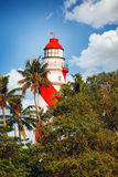 Thangassery Lighthouse on the cliff surrounded by palm trees and big sea waves on the Kollam beach. Kerala, India Royalty Free Stock Photo