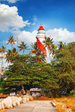 Thangassery Lighthouse on the cliff surrounded by palm trees and big sea waves on the Kollam beach. Kerala, India Royalty Free Stock Image