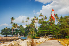 Thangassery Lighthouse on the cliff surrounded by palm trees and big sea waves on the Kollam beach. Kerala, India Royalty Free Stock Photography