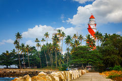 Thangassery Lighthouse on the cliff surrounded by palm trees and big sea waves on the Kollam beach. Kerala, India Royalty Free Stock Photos